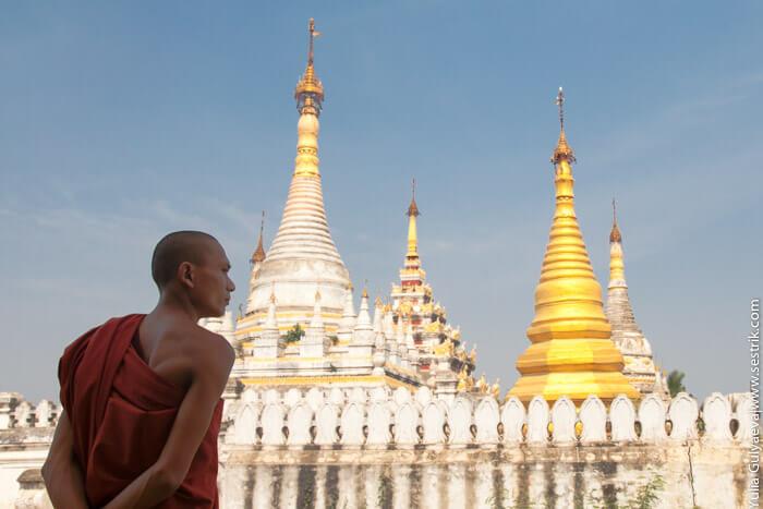 монах в бирме на фоне золотой ступы монастыря Маха Aungmye Bonzan в инве