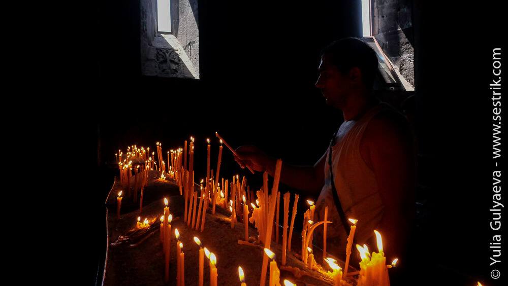 армяне ставят свечи в монастыре гегард