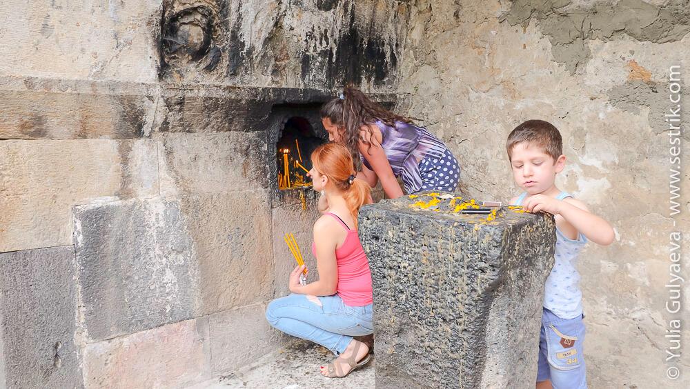 армяне ставят свечки в монастыре в ардви